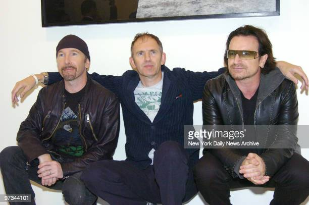 Photographer Anton Corbijn is flanked by U2's Bono and The Edge at the Stellan Holm Gallery on W 24th St during the opening reception for his exhibit...