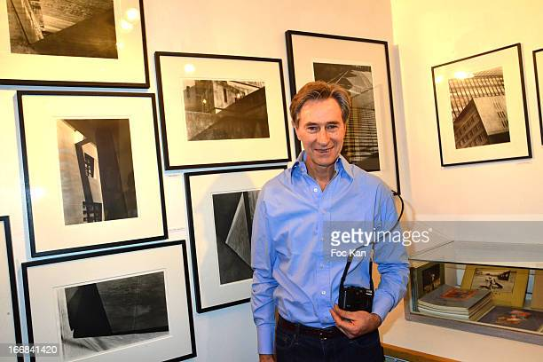 Photographer Aramy Machry poses with his works during 'Les Racines De La Ville' Aramy Machry' s Photo Exhibition Preview At 'Le Plac Art' Gallery on...
