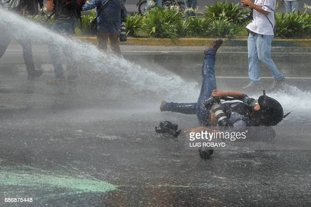 AP photographer Ariana Cubillos is knocked down by the water jet of a riot control vehicle as opposition activists clash with riot police during a...