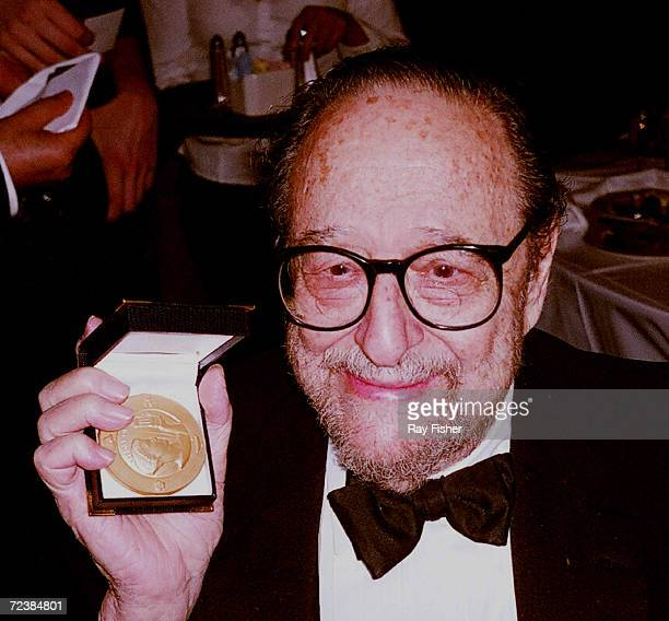 Photographer Arnold Newman holding Gold Medal Award of Honor which he received at National Arts Club