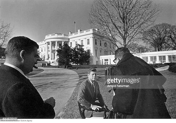 Photographer Arnold Newman photographs President John F Kennedy in front of the White House as Press Secretary Pierre Salinger looks on December 12...