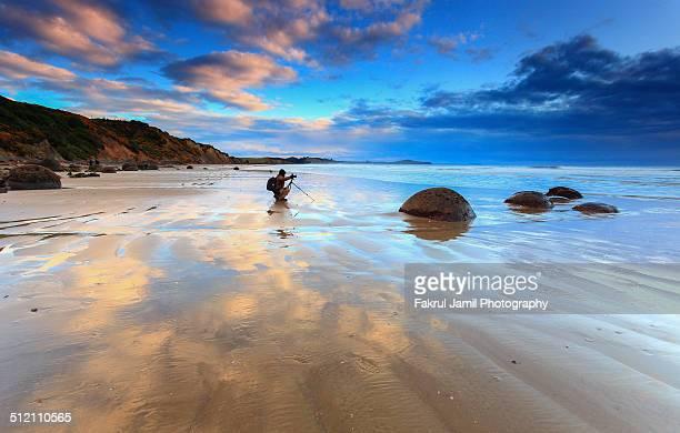 A photographer at Moeraki Boulders, New Zealand