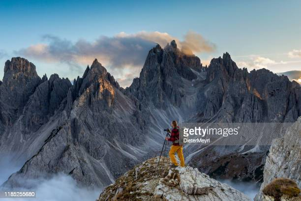 photographer at tre cime di lavaredo with cima cadin di san lucano in background - unesco stock pictures, royalty-free photos & images