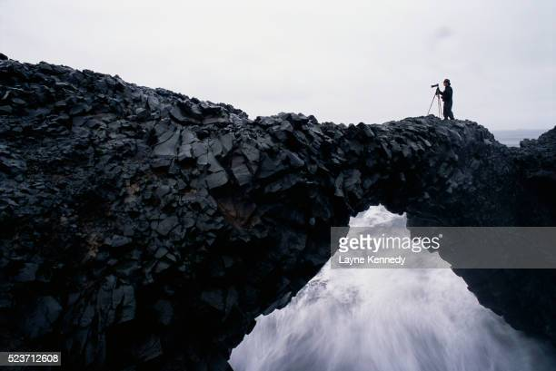 Photographer atop Natural Arch in Iceland