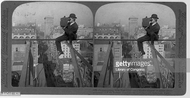 A photographer balances 18 stories above the ground while photographing scenes of New York ca 1907 New York City