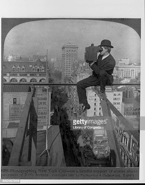 A photographer balances eighteen stories above Fifth Avenue while he uses a stereoscopic camera to take pictures of the city ca 1905 New York City