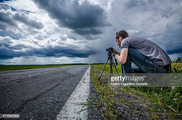 photographer beside a country road - 三脚 ストックフォトと画像