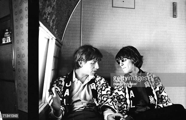 Photographer Bob Whitaker and George Harrison share a moment aboard the Beatles' plane to Japan 29th June 1966 They are wearing Happi coats provided...
