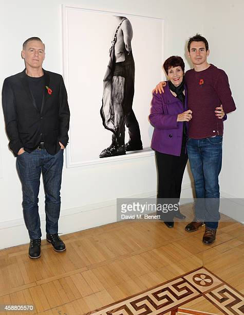Photographer Bryan Adams poses with Injured ExServiceman Jaco Van Gass and mother Aloma Van Gass at the private view of 'Wounded The Legacy of War'...