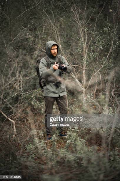photographer camouflaged on nature between bushes raising the camera - hunting stock pictures, royalty-free photos & images
