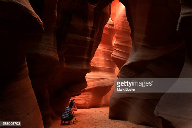 A photographer carefully makes a picture using the graceful swirling walls and ceilings of Antelope Canyon near Page Arizona as his composition...