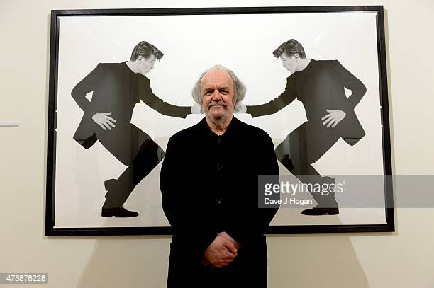 Photographer Chalkie Davies poses in front of his photograph of David Bowie at the Chalkie Davies The NME Years Exhibition on May 15 2015 in Cardiff...