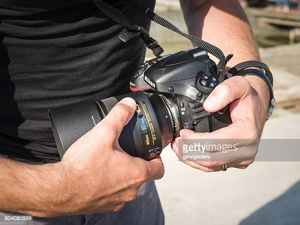 photographer changing lens - nikon stock pictures, royalty-free photos & images
