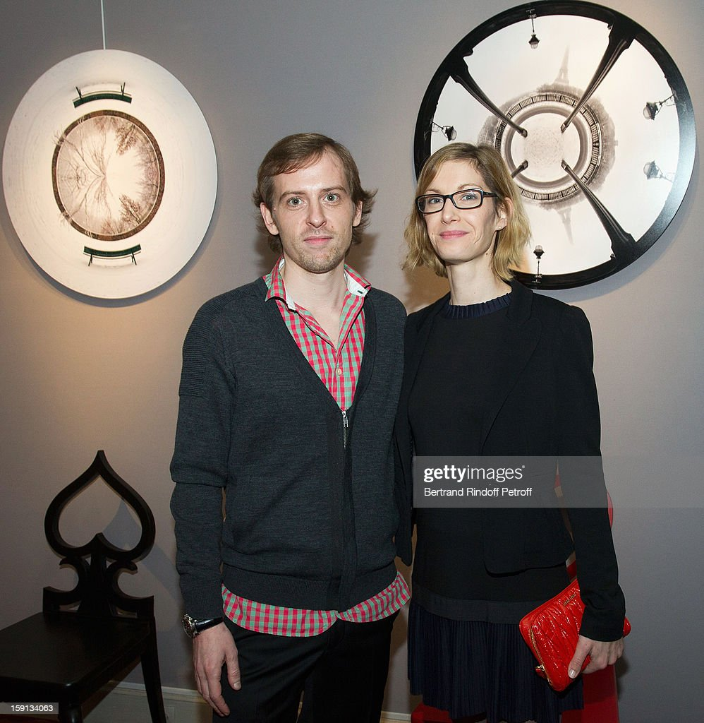 Photographer Charles Maze (L) and his partner pose by two of Maze's photographs during the 'Sorcieres' (Witches) exhibition preview at Galerie Pierre Passebon on January 8, 2013 in Paris, France.