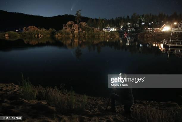 Photographer checks his camera display while photographing Comet NEOWISE , also known as 'C/2020 F3', at Big Bear Lake after sunset on July 19, 2020...