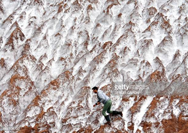 A photographer clambers along mounds of potassium waste from the local salt mine in the town of Soligorsk some 140 km south from Minsk on September...