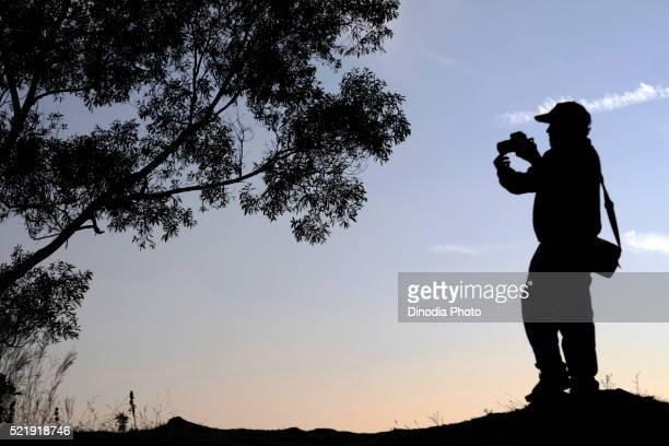 Photographer clicking image in silhouette, Madikeri, Coorg, Karnataka, India
