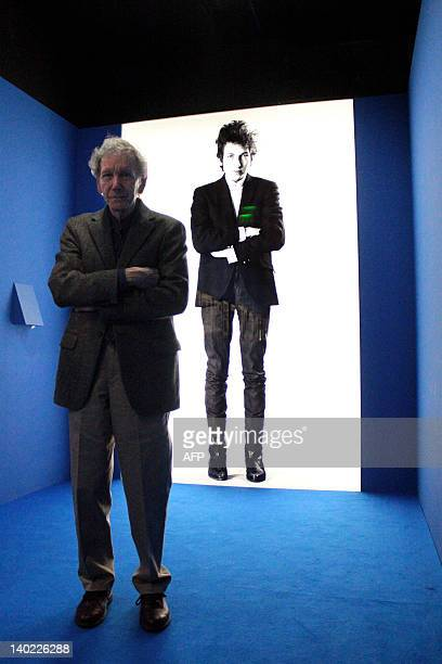US photographer Daniel Kramer poses in front of a picture of US singer and songwriter Bob Dylan displayed on March 1 2012 at the Cite de la Musique...