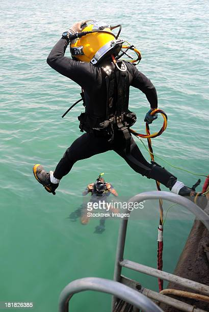 a photographer documents a navy diver as he enters the water. - scaphandrier casque photos et images de collection