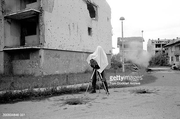 Photographer documents war damage on a large format camera in a devastated suburb of Sarajevo. During the 47 months between the spring of 1992 and...