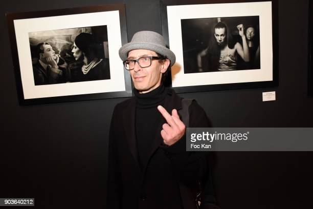 Photographer Dom Garcia poses with the work of Nan Goldin during 'A Mon Seul Desir 20 Ans de Mauvais Genres chez Agnes B' Exhibition Finale at Agnes...