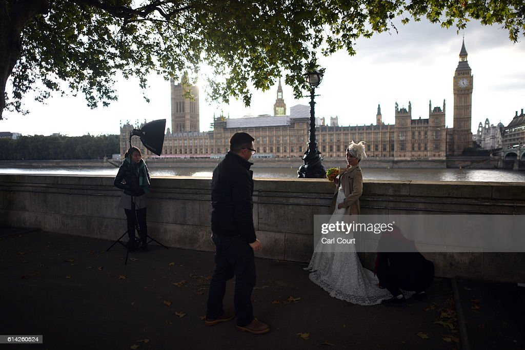 Photographer Dominic Wu looks on as adjustments are made to Echo Li's dress during a pre-wedding photography shoot opposite the Palace of Westminster on October 11, 2016 in London, England. It's a Chinese custom for couples to have their wedding photos taken before they are married and on the wedding day the photos will be shown to guests on cards and big screens. Photography studios such as J.R Studios in east London have seen business boom as the capital has become increasingly popular as a location for pre-wedding photography thanks in part to its instantly recognisable landmarks.