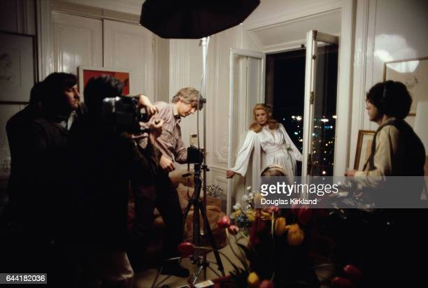 Photographer Douglas Kirkland adjusts his camera to shoot actress Catherine Deneuve in a Paris apartment