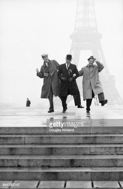 Photographer Douglas Kirkland and journalists Art Buchwald and Jack Star kick up their heels together in front of the Eiffel Tower on a foggy day