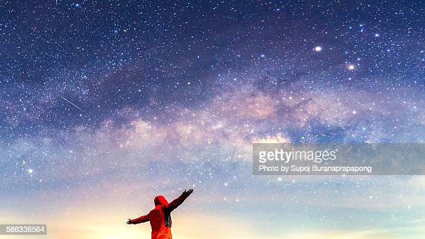 photographer extend his arms under the milkey way - milky way stock pictures, royalty-free photos & images