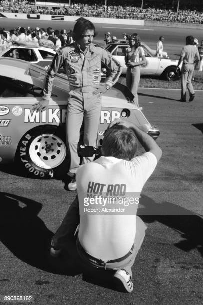 A photographer for Hot Rod Magazine takes a picture of NASCAR driver Dale Earnhardt Sr prior to the start of the 1980 Firecracker 400 NASCAR race at...
