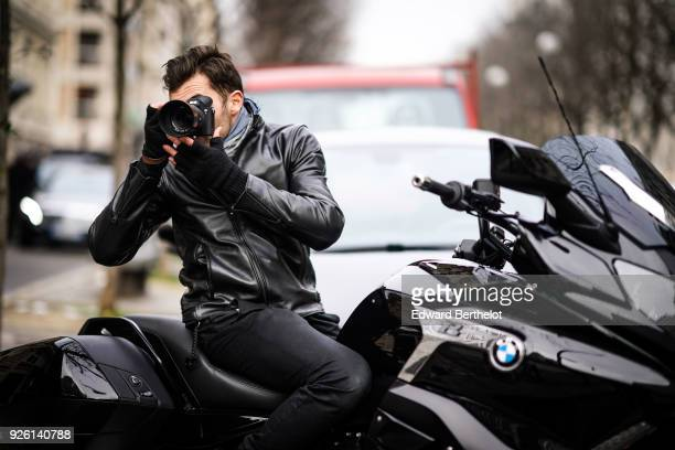 Photographer Francois Xavier Watine wears a black leather jacket and is using a Sony Alpha 7r iii mirrorless camera on a BMW black motorbike during...