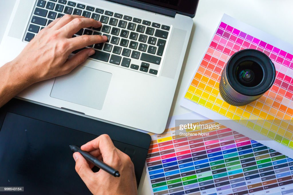 Photographer Graphist Designer Working On A Laptop With Colors Chart