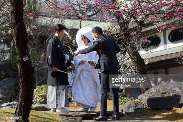 Photographer guides newlyweds in posing for the photo shoot at Yushima shrine.