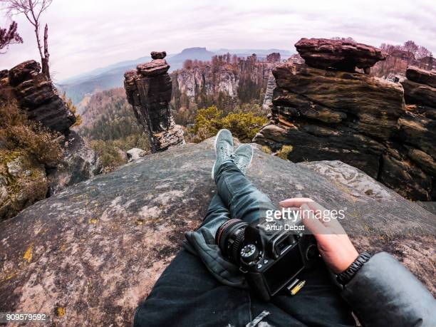Photographer guy from personal perspective doing hiking, resting from viewpoint with photography camera in the beautiful Saxon National Park in Germany with stunning views of the rock formations with vertigo and adrenaline sensations.