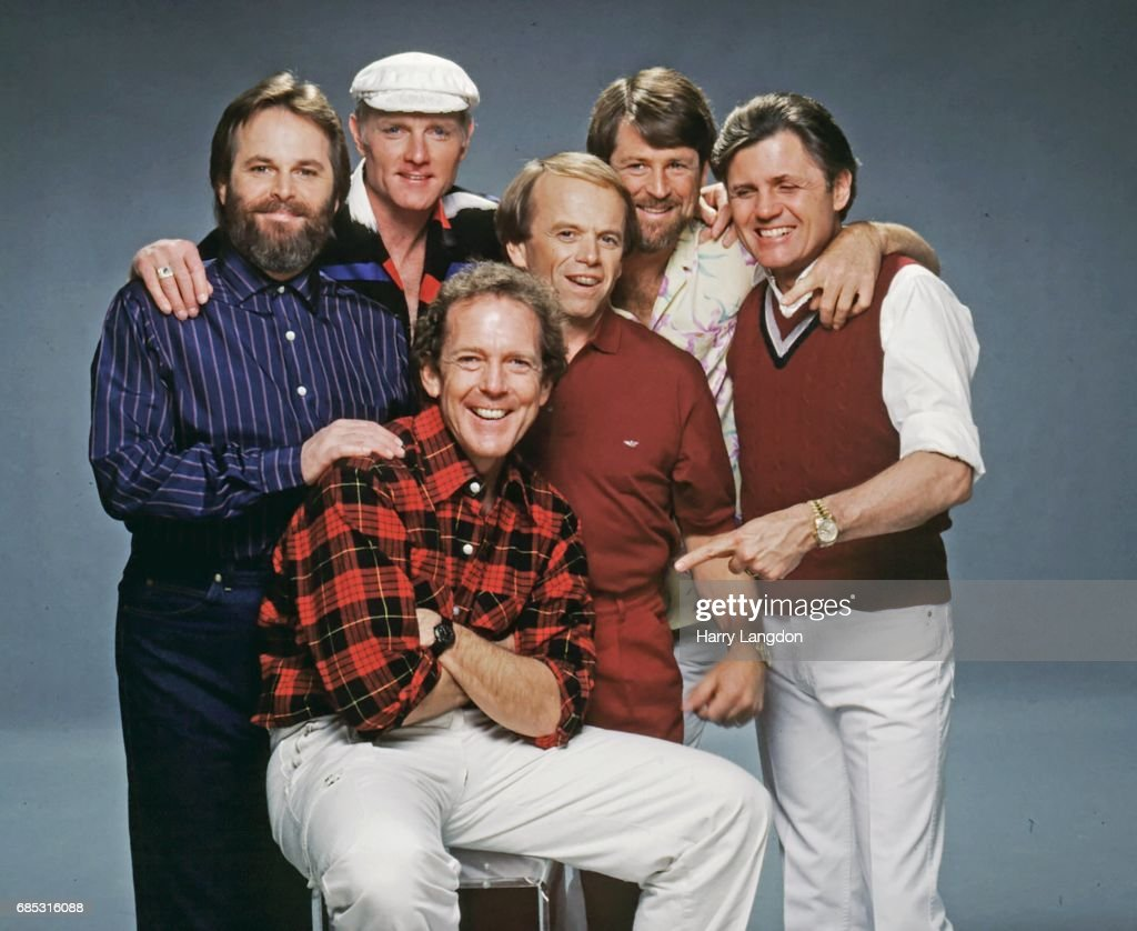 Photographer Harry Langdon (seated) poses for a portrait with the Beach Boys (L-R) Carl Wilson, Mike Love, Al Jardine, Brian Wilson and Bruce Johnston in 1987 in Los Angeles, California.