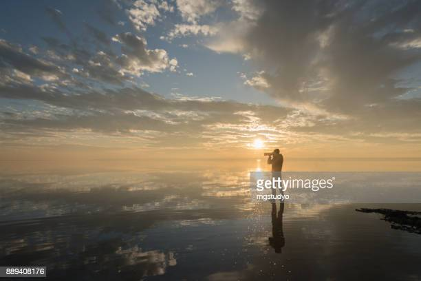 Photographer  having fun walking on salt lake at sunset