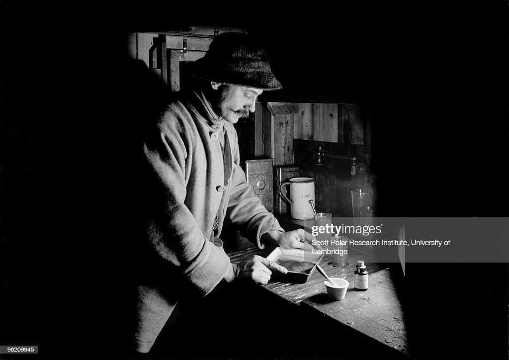 Photographer Herbert Ponting (1870 - 1935) in his makeshift darkroom in the Winterquarters Hut, Ross Dependency of Antarctica, during Captain Robert Falcon Scott's Terra Nova Expedition to the Antarctic, 22nd July 1911.