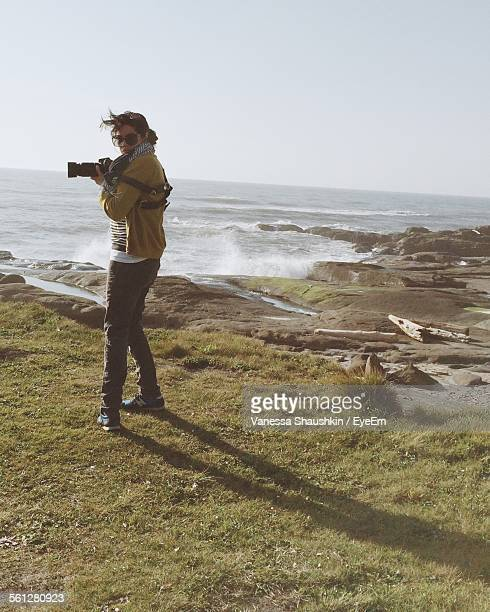 Photographer Holding Camera While Standing On Grassy Field By Sea Against Clear Sky