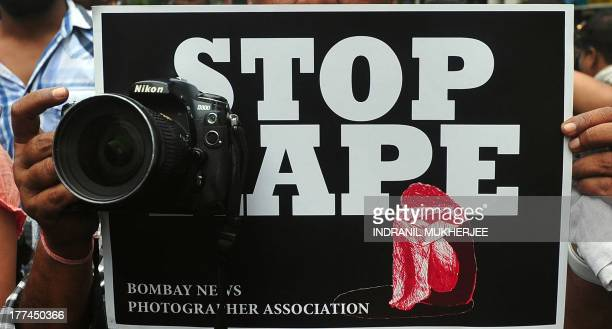 A photographer holds a placard during a protest against the the gangrape of a colleague in Mumbai on August 23 2013 Five men gangraped a woman...