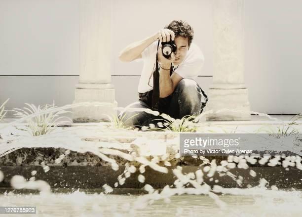 photographer in action. squatting to take a photo of a fountain - victor ovies fotografías e imágenes de stock