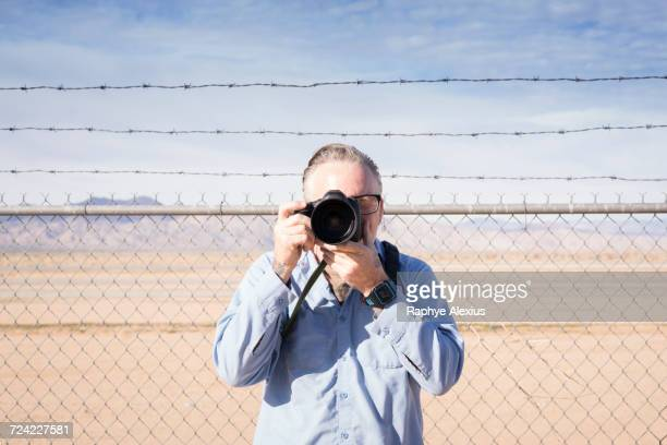 Photographer in front of barbed wire fence in desert taking photograph, California, USA