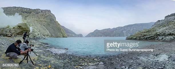 Photographer in Gas Mask take photo of acid lake at Kawah Ijen