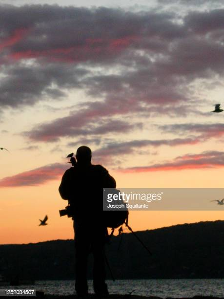 photographer in silhouette at hudson river - joseph squillante stock pictures, royalty-free photos & images