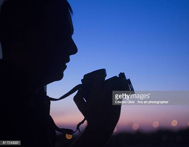 Photographer in silhouette at sunset and sky