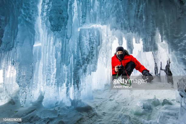 Photographer in the ice cave at sunset. Baikal, Russia