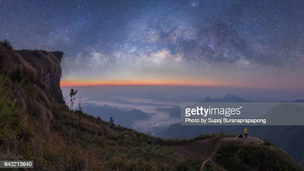 Photographer in yellow jacket take photo of beautiful milky way before sunrise on the mountain peak - high resolution