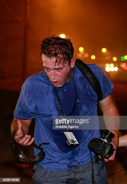 A photographer inhaling tear gas fired by police officers reacts during a protest on August 18 2014 for Michael Brown who was killed by a police...