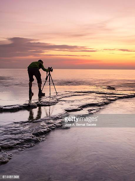Photographer  inside the water of the sea on the coast, extracting a photo of the colors of the dawn