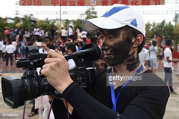 Photographer is daubed rice ash on face during the Face Painting Festival in Puzhehei Resort of Qiubei County on July 18, 2016 in Wenshan Prefecture,...