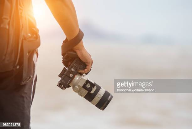 photographer is holding a camera - fotograf stock-fotos und bilder